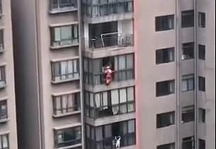Фото №1 - В Китае Человек-пожарный спустился на веревке с 16 этажа, чтобы спасти стоявшую на карнизе девочку (видео)