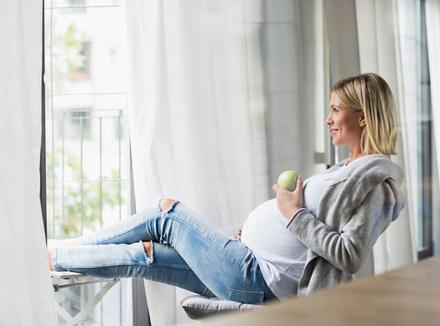 Беременная женщина ест яблоко