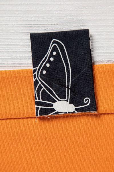 Отрез оранжевой ткани подгибают с обеих сторон сначала на 1 см, затем на 5 см и прострачивают. Черные заготовки сгибают пополам, равномерно распределяют по обеим сторонам оранжевого полотна, приметывают и прострачивают крест-накрест.