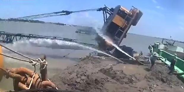 Фото №1 - Под тяжестью груза экскаватор переворачивается и падает в реку (видео)
