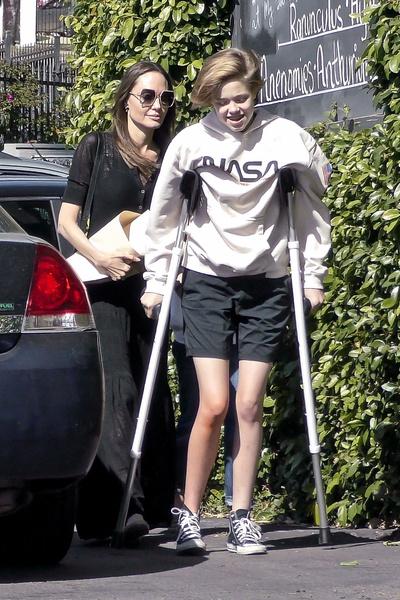 Фото №1 - «Трудная» дочь Джоли и Питта снова встала на костыли через год после операции на бедре