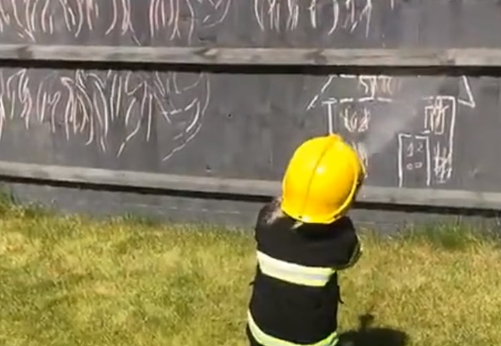 Фото №1 - Маленькая девочка, готовясь стать пожарным, спасает куклу и тушит нарисованный дом (видео)
