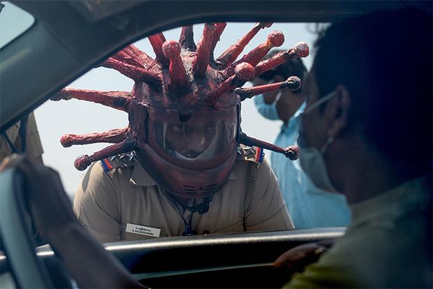 Фото №1 - Индийский полицейский пугает нарушающих карантин коронашлемом