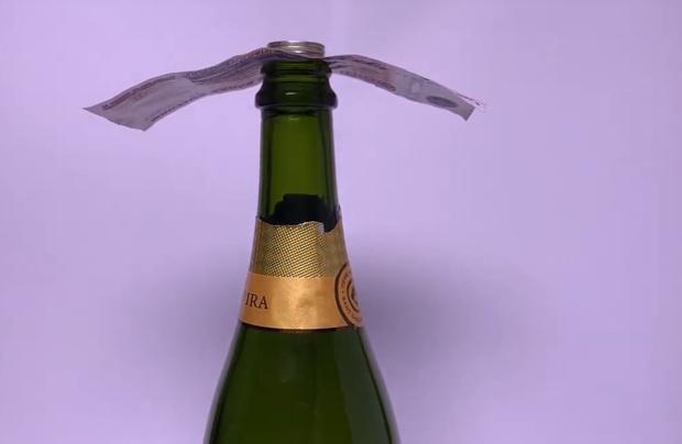 Фото №1 - Фокус: как вытащить купюру из-под стопки монет на горлышке бутылки, не уронив их (видео)