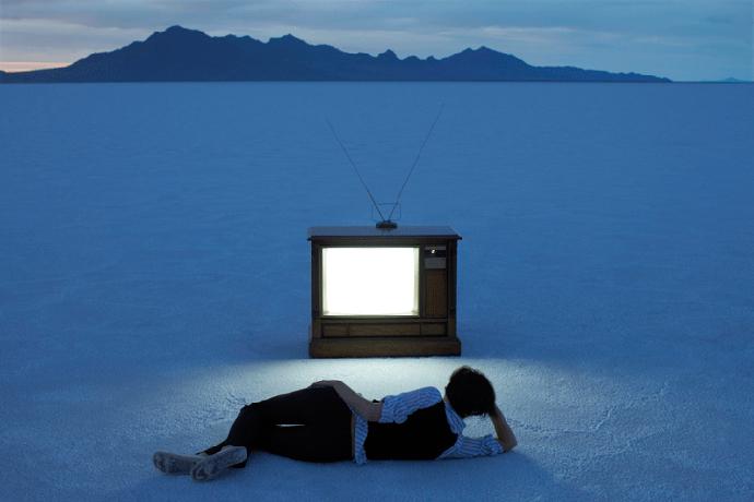 Человек на пляже перед телевизором