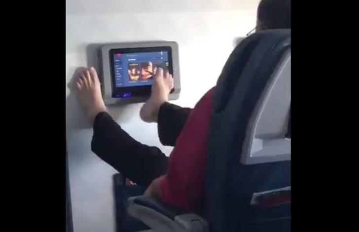 Фото №1 - Самое оскорбительное видео недели: пассажир управляет мультимедиа-системой в самолёте ногами