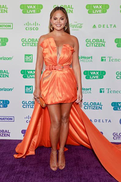 Фото №1 - Фея хурмы: топ-модель Крисси Тейген в шелковом оранжевом мини-платье с очень длинным шлейфом