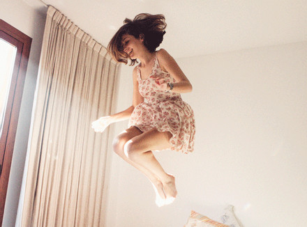 Девушка, прыгающая на кровати