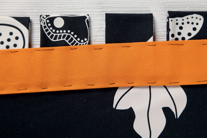 Два полотна соединяют изнанкой внутрь и прострачивают с 2,5-сантиметровым подгибом. По коротким сторонам пришивают оранжевые ленты.
