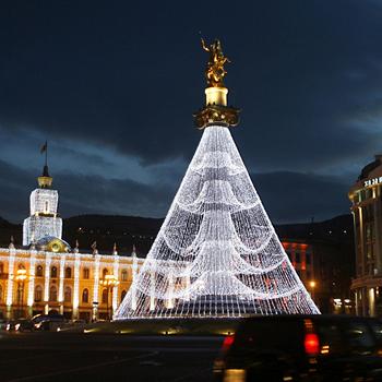 Иллюминация в виде новогодней елки украшает монумент Святого Георгия на площади Свободы в Тбилиси.