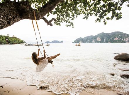 Женщина на качелях на пляже