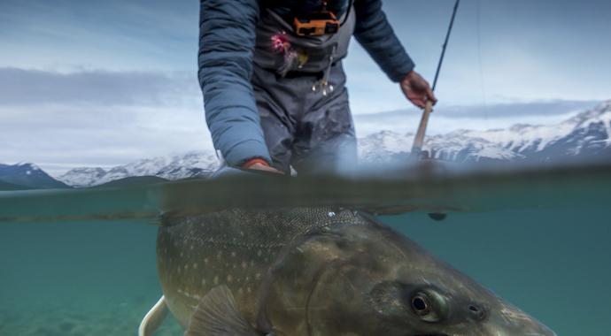 Рыбак из Белоруссии невозмутимо ловит рыбу в окружении огня