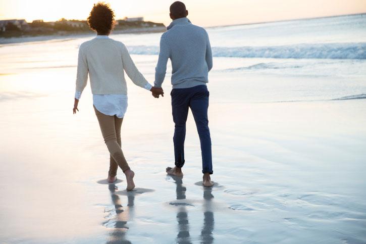 Пара прогуливается по берегу