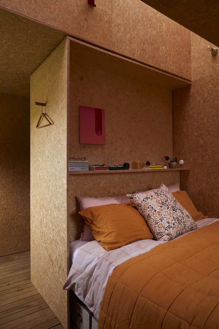 Спальня хозяев скрывается в нише, выполненной из древесно-стружечных плит.