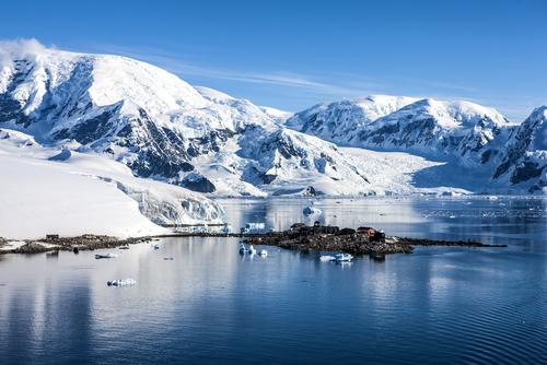 ShutterstockНесмотря на то, что летом Антарктика получает примерно на 7% больше солнечного тепла, чем Арктика, климат в последней значительно теплее, чем в Южной полярной области. Есть несколько причин, объясняющих это на первый взгляд странное явление. Одна из них — свободное сообщение Северного Ледовитого океана с Атлантическим на обширном пространстве между Гренландией и северной оконечностью Европы. Теплые воды Атлантики, в том числе мощный Гольфстрим, свободно проникая под арктические льды, отдают колоссальное количество тепла Арктике, чем значительно смягчают ее климат. Кроме того, вместе с пресной водой впадающих в Северный Ледовитый океан крупнейших рек Евразии и Северной Америки, Арктика круглый год получает дополнительное количество тепла, которого лишена Антарктика. Но, пожалуй, одна из главных причин антарктического холода заключается в том, что существующий у Южного полюса материк, является самым высоким из всех шести, имеющихся на Земле. Средняя высота Антарктического континента составляет более 2 000 м, тогда как следующая за ним по высоте Евразия имеет среднюю высоту всего около 900 м. Этот факт объясняется тем, что материковые породы Антарктиды покрывает мощный слой льда, средняя толщина которого составляет примерно 1 800 м. Тогда как в Центральной Арктике высота поверхности ледяных полей акватории Северного Ледовитого океана составляет считанные метры, что практически соответствует уровню моря. Только за счет разности высот Антарктида должна быть холоднее Арктики в среднем примерно на 13°С, а на вершине ледяного купола — на целых 25—28°С, так как температура воздуха в атмосфере убывает на 6,5° с каждым километром высоты.