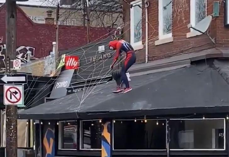 Фото №1 - В Канаде некто в костюме Человека-Паука залез на крышу, начал плести паутину и болтать с прохожими (видео)